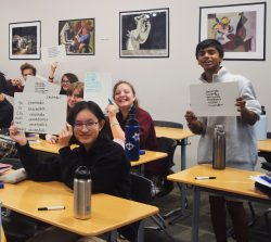 Foreign language students, seated at their desks, holding up white boards with their language translations